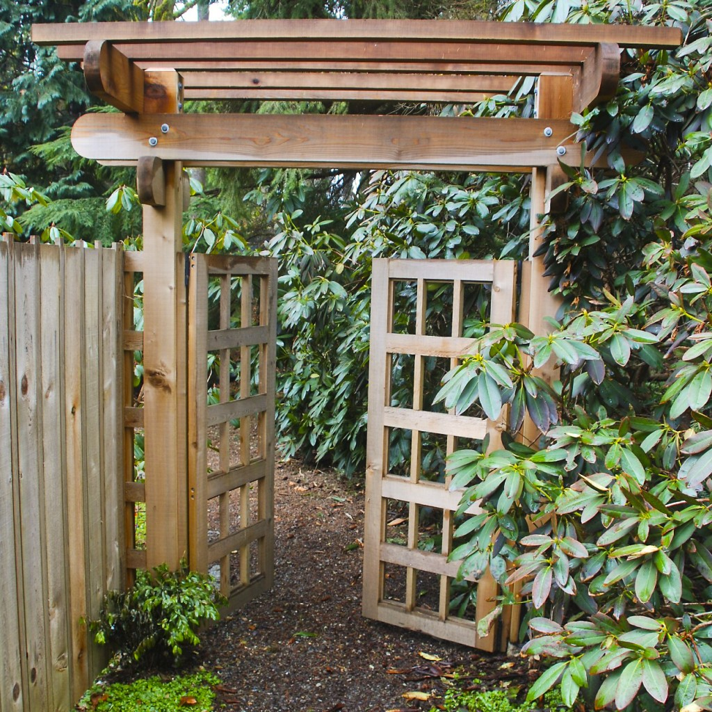 Wood fence, gate, and walkway through rhododendron garden